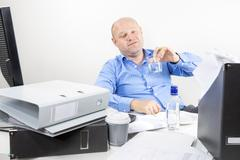 Drunk businessman drinks alcohol at the office Kuvituskuvat