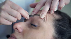 Woman getting tweezing her eyebrows by beautician HD Stock Footage