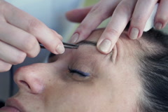Woman getting tweezing her eyebrows by beautician NTSC Stock Footage