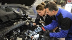 Mechanics instructor teaching woman in apprenticeship - stock footage