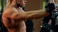 Side view of muscular man training his hands in the gym, slow motion Stock Footage