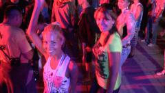 two young girls dancing and smiling for the camera at a big rave party - stock footage