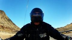 Backlit Helmeted Motorcycle Rider On Desert Highway Stock Footage