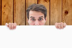 Composite image of attractive young man smiling and holding poster Stock Photos