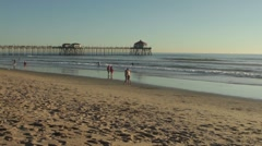 Long Angle of Huntington Beach Pier with People Walking by Ocean Waves Stock Footage