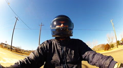 Helmeted Motorcycle Rider In Small Town- Blue Jacket Stock Footage