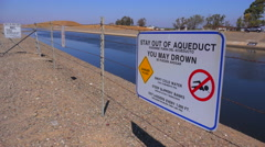 Signs warn people to stay out of the California aqueduct. Stock Footage