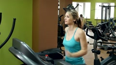 Athletic girl doing an exercise on running track in the gym Stock Footage