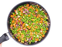 Frying vegetables in a fry pan, peas, red onion and corn - stock photo
