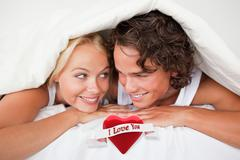 Composite image of couple under a duvet with a knowing smile - stock illustration