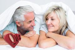 Composite image of closeup of a mature couple lying in bed - stock illustration