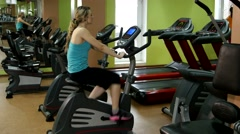 Athletic and attractive girl in fitness hall is cycling Stock Footage