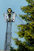 Fireman with helmet on the big ladder is clearing fire Stock Photos