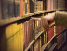 hand in store with antique books - stock photo