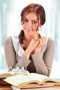 Young woman reading a book. Female student learning. - stock photo