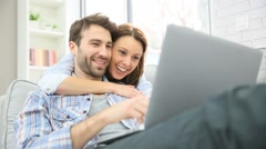 Couple in sofa websurfing with laptop - stock footage