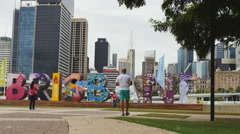 Tourists admire the iconic Brisbane sign slow motion Stock Footage
