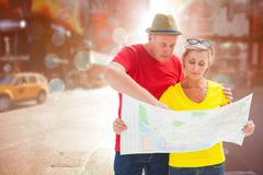 Composite image of lost tourist couple using map - stock photo