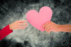 Composite image of couple passing a paper heart Stock Photos