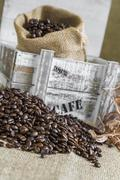 scattered coffee beans around wooden box with a burlap bag - stock photo
