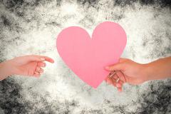 Stock Photo of Composite image of couple passing a paper heart