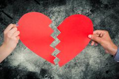Composite image of two hands holding broken heart - stock photo