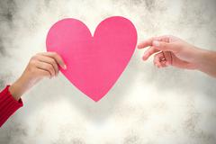Composite image of couple holding a heart - stock photo