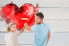 Composite image of young couple painting with roller Stock Photos