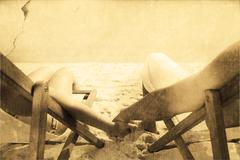 Composite image of couple resting on deck chairs - stock photo