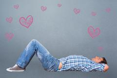 Composite image of young man lying on floor thinking Stock Photos