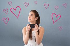 Composite image of thoughtful brunette holding her phone Stock Photos