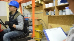Operator with overseer working in warehouse Stock Footage