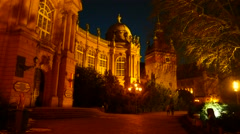 People pass by at the Vajda Hunyad Castle in Budapest at night Stock Footage