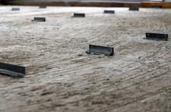 Steel angle on cement floor - stock photo