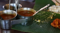 Man pours out dressings onto Indian food on banana leaf Stock Footage