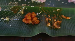 Man eats up food and rolls up banana leaf Stock Footage