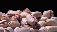 4K pile of pistachios rotating smoothly on black background, tripod used unde - stock footage