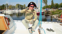 Young adult funny pirate hat on, yachts in marina, recreation Stock Footage