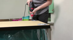 Installing holders for table legs on wooden surface, man with drill working Stock Footage