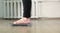 Human legs standing on weight scale in clear domestic room Stock Footage