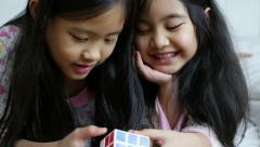 4K Video : Little Asian girls playing rubik cube on the bed together Stock Footage