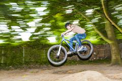 Child has fun jumping with thé bike over a ramp Stock Photos