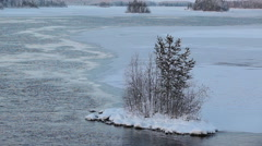 Island in snow on the middle of flowing water of wide watercourse of winter lake - stock footage