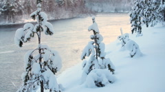 Stock Video Footage of Wide river flowing in snowy forest at winter season in sunset light. Karelia rep