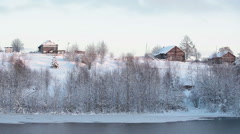 Timber houses of Russian village on the hill at winter season. Unfrozen river Stock Footage