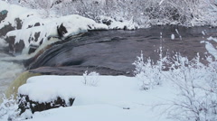 Water flowing through the rock watercourse at winter season. Plain waterfall - stock footage