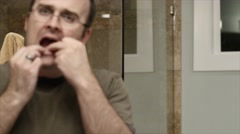 Man flossing his teeth Stock Footage