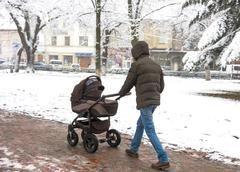 Father with a small childin the stroller walking down the street. Intentional - stock photo