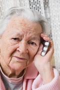Old sad woman with pills at home Stock Photos