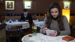 Laughing girl having tea in a coffee shop and boy reads an interesting book Stock Footage